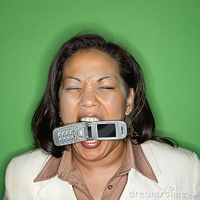 Businesswoman biting cellphone.