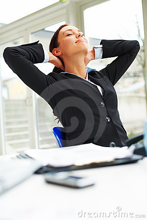 Businesswoman in black suit relaxing in the office
