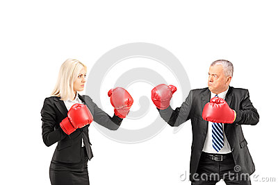 Businesswoman and businessman with boxing gloves having a fight