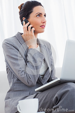 Businesswoman calling with her mobile phone and using laptop sit