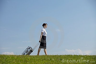 Businesswoman carrying luggage in park