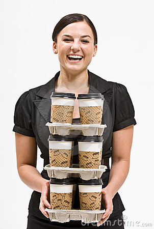 Businesswoman carrying stack of coffee cups