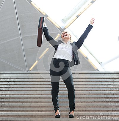 Businesswoman celebrating arms outstretched on staircase