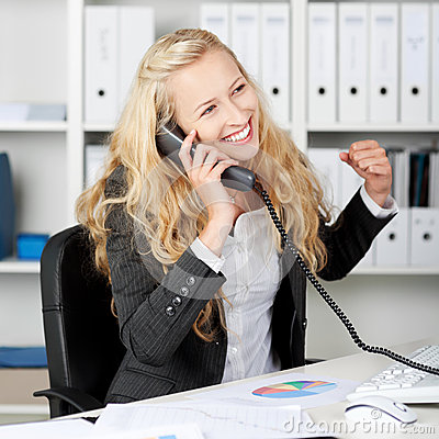 Businesswoman With Clenched Fist Communicating On Landline Phone
