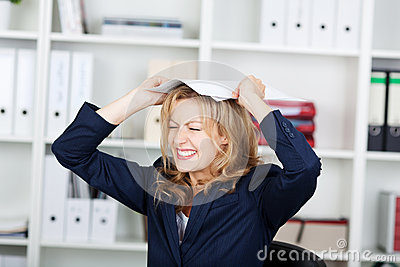 Businesswoman Clenching Teeth While Placing Documents On Head