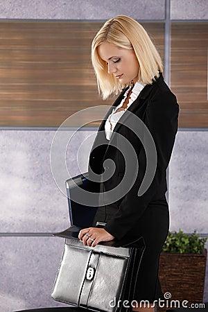Businesswoman closing briefcase