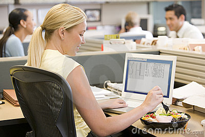 Businesswoman in cubicle using laptop and eating s