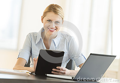 Businesswoman With Digital Tablet And Laptop Sitting At Desk