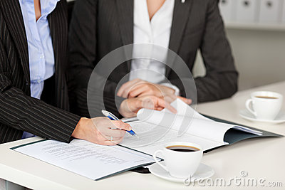 Businesswoman Explaining Documents To Female Coworker At Desk