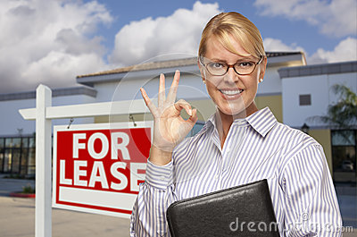 Businesswoman In Front of Office Building and For Lease Sign