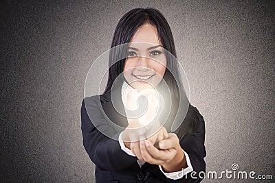 Businesswoman give lit lightbulb