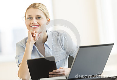 Businesswoman With Hand On Chin Holding Digital Tablet In Office