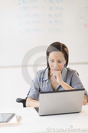 Businesswoman With Hand On Chin Using Laptop In Office