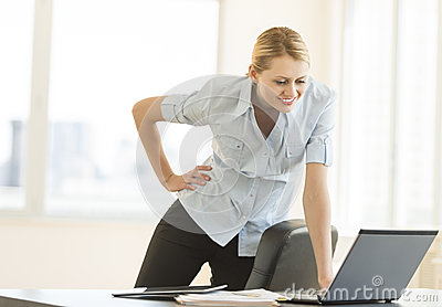 Businesswoman With Hand On Hip Looking At Laptop In Office