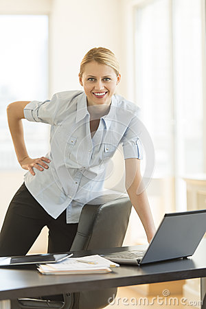 Businesswoman With Hand On Hip Standing By Desk