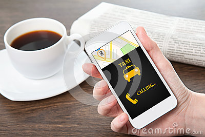 Businesswoman hand holding a phone with interface taxi in the of