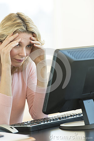 Businesswoman With Head In Hands Looking At Computer