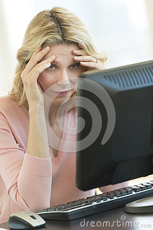 Businesswoman With Head In Hands Looking At Computer Monitor