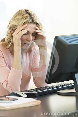 Businesswoman With Head In Hands Sitting At Desk