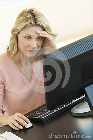 Businesswoman With Head In Hands Using Computer At Desk