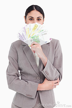 Businesswoman hiding her face behind bank notes