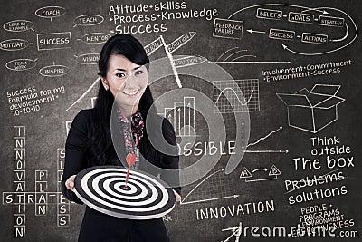Businesswoman hold bull s eye in class