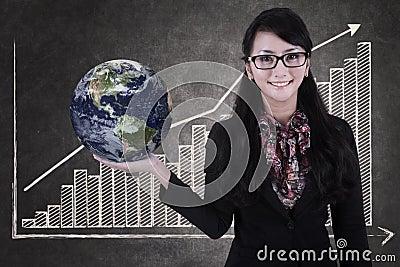 Businesswoman hold globe on growing bar chart chalkboard