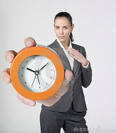 Businesswoman holding and showing alarm clock