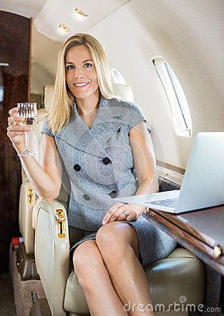 Businesswoman Holding Wineglass In Private Jet