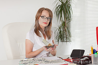 Businesswoman holds nest with golden egg, money. Stock Photo