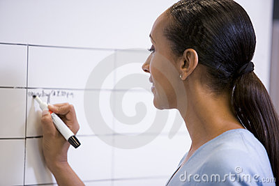 Businesswoman indoors writing on erasable board
