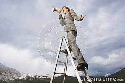 Businesswoman On Ladder Shouting Through Megaphone
