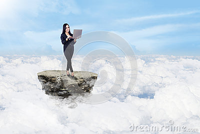Businesswoman and laptop above clouds