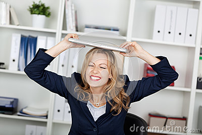 Businesswoman With Laptop On Head Clenching Teeth