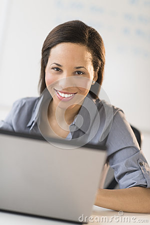 Businesswoman With Laptop Sitting At Desk In Office