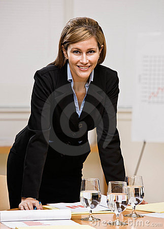 Businesswoman leaning on table in conference room