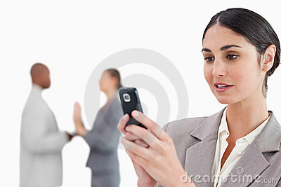 Businesswoman looking at cellphone with colleagues behind her