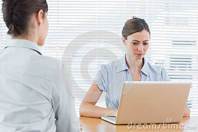 Businesswoman looking at laptop during an interview