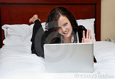 Businesswoman Lying on Bed With Laptop