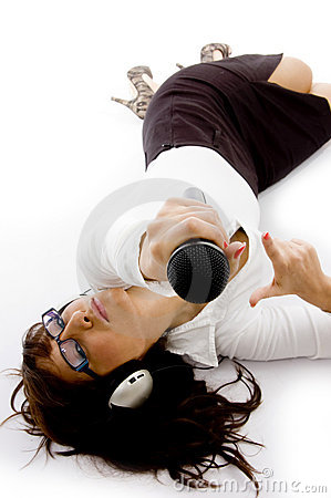 Businesswoman lying down holding a microphone