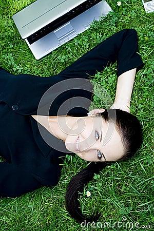 Businesswoman lying on grass