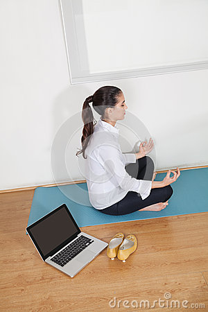 Businesswoman meditating in office