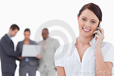 Businesswoman with mobile phone and co-workers