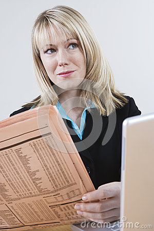 Businesswoman With Newspaper And Laptop