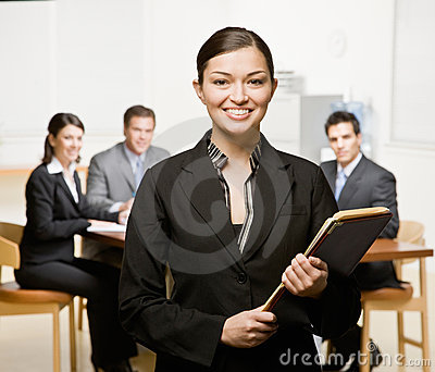 Businesswoman with notebook and co-workers