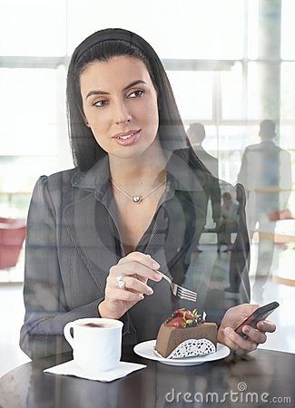 Businesswoman in office cafe having cake