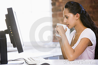 Businesswoman in office drinking coffee