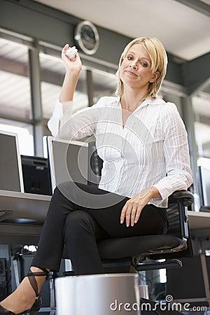Businesswoman in office throwing garbage in bin