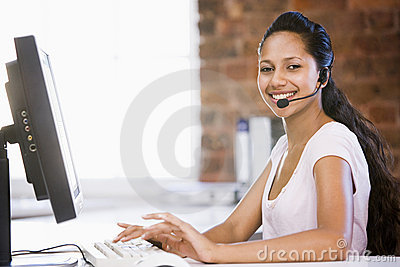 Businesswoman in office wearing headset and typing