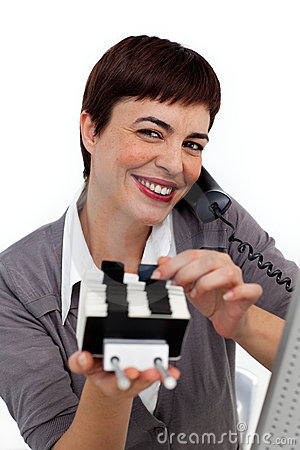 Businesswoman on phone consulting a business card